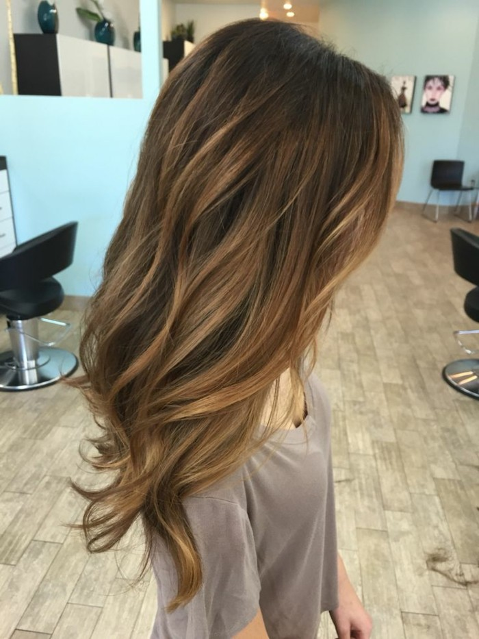 caramel highlights on a brunette, medium length wavy hair, balayage dark hair, on a slim woman, dressed in grey