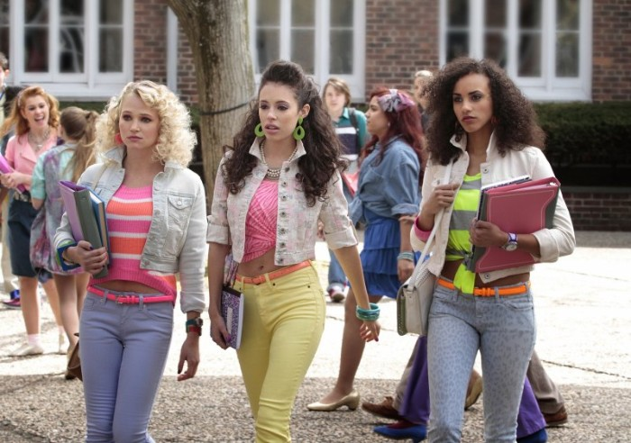 female students dressed in 80s clothes, skinny trousers in blue and yellow, striped and patterned tops in popping colors, retro hairstyles and jewelry