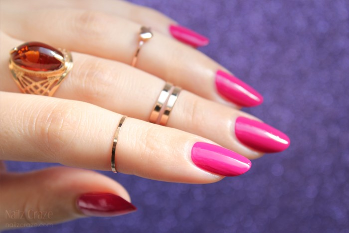 oval shaped nails, in hot pink, on a pale hand, with several golden rings, one of which features a large amber stone