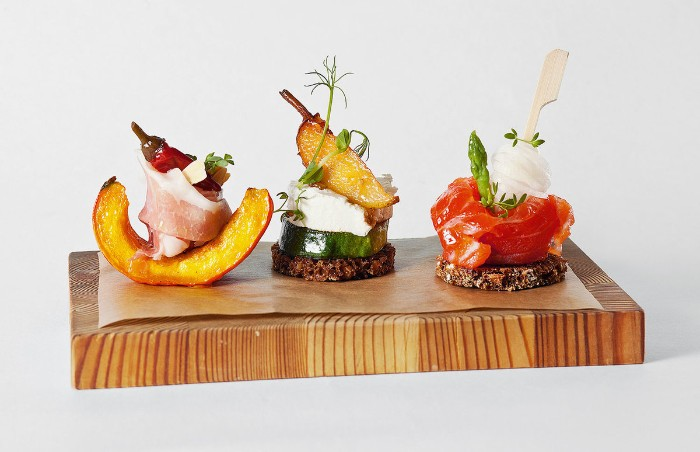 thick wooden block, with three artisan canapes, baked peach with prosciutto, tomato with asparagus, pear with ricotta, appetizers for a crowd