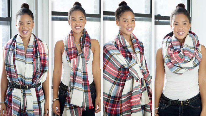 top knot worn by a smiling brunette woman, with a white tank top, and black trousers, demonstarting different ways to wear a bulky patterned scarf
