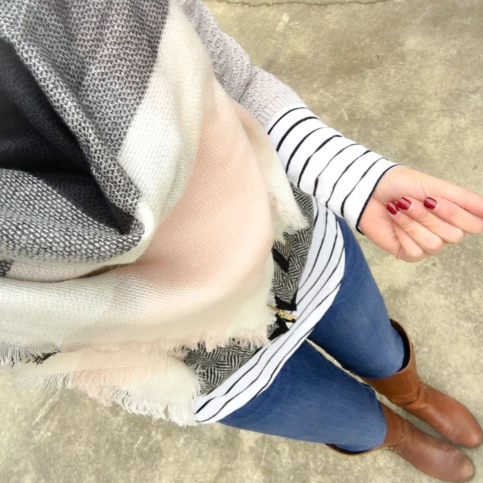 high angle view, of a woman in skinny jeans, and brown leather boots, wearing a striped jumper, and a soft grey, white and pale pink shawl, how to tie a blanket scarf, fast and easy