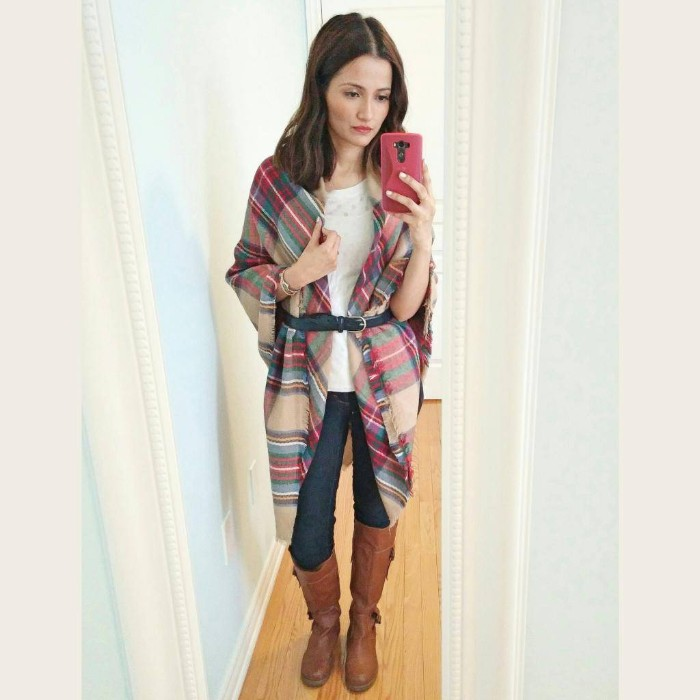cardigan made from a tartan scarf, draped over the shoulders of a woman, and secured with a black leather belt, how to fold a blanket scarf, over dark skinny jeans, white top and brown leather riding boots