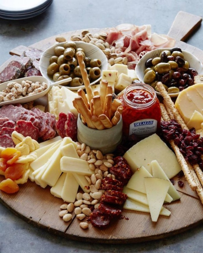 bread sticks and nuts, salami and cheeses, on a big round wooden platter, with dried fruit olives, and different dips