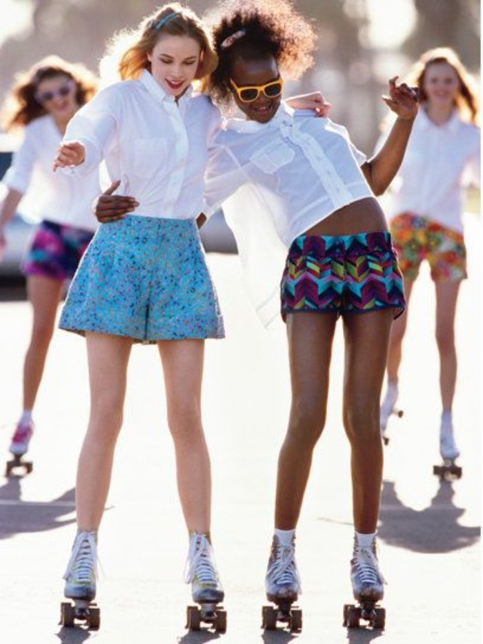 slender young women, dressed in white shirts, and patterned shorts, skating with vintage roller skates, while hugging