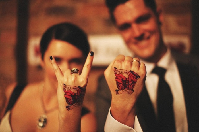 smiling couple in formal attire, showing the backs of their hads to the camera, they have identical tattoos, in black and red and yellow, husband and wife tattoos