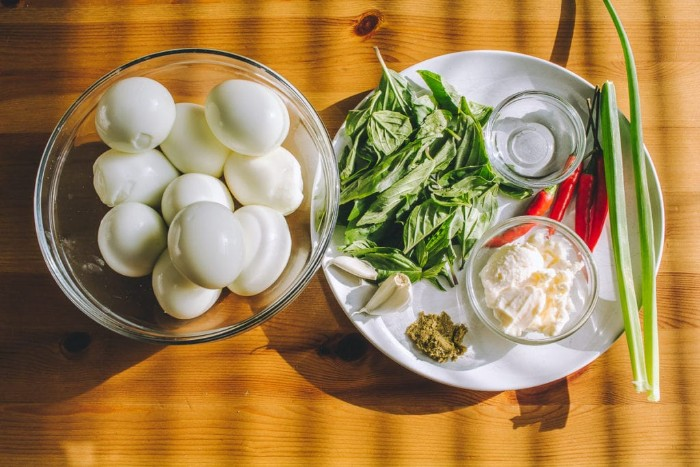 glass bowl filled with hardboiled eggs, next to a white plate, containing ingredients for horderves, mayo and garlic cloves, spring onion and chilis, basil and pesto