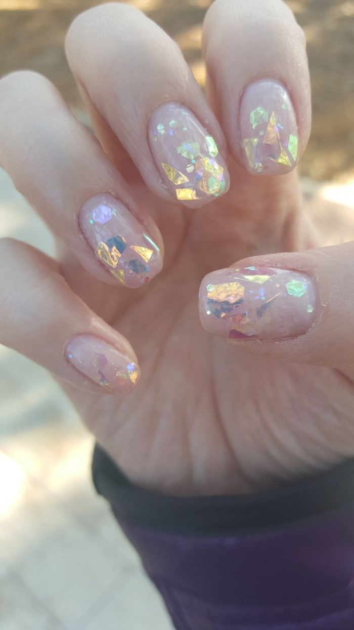 large flakes of iridescent glitter, on the square manicure of a hand, with folded fingers, and nude pink nail polish