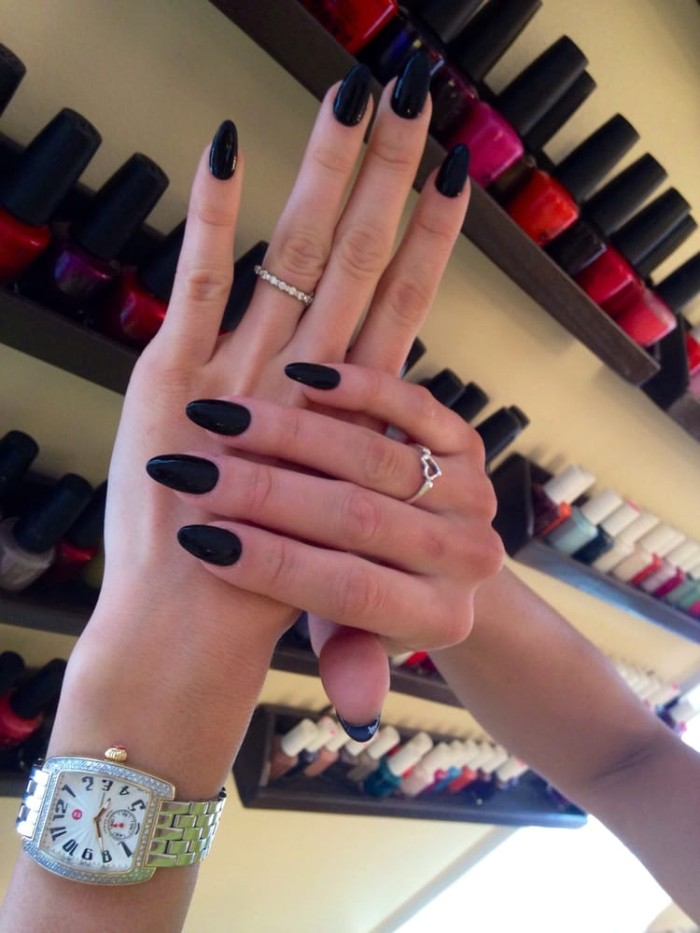 watch and two rings, worn by two slim hands, with long fingers, and a long oval manicure, painted in black nail polish