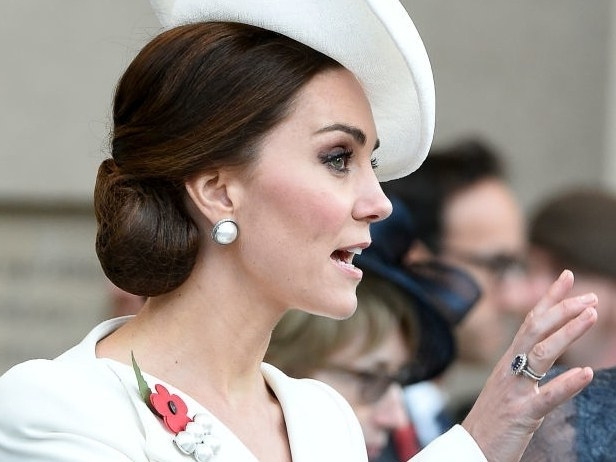 white hat and coat, decorated with a red poppy badge, worn by kate middleton, hand with a large ring, and nude nails