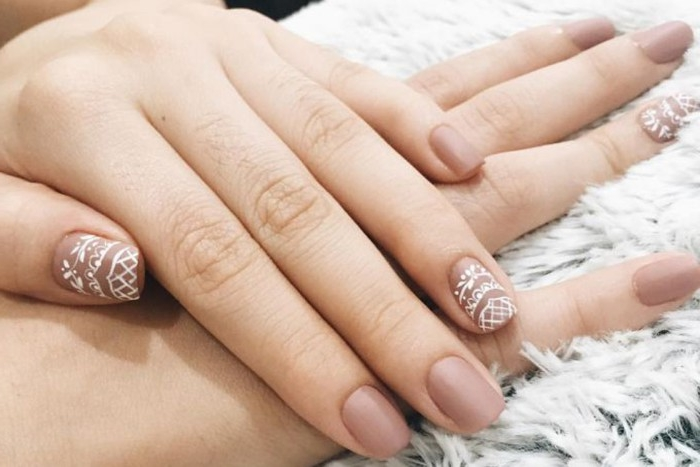ash pink nail polish, with white lace-like, hand-drawn motifs, on nude matte nails, attached to two pale hands
