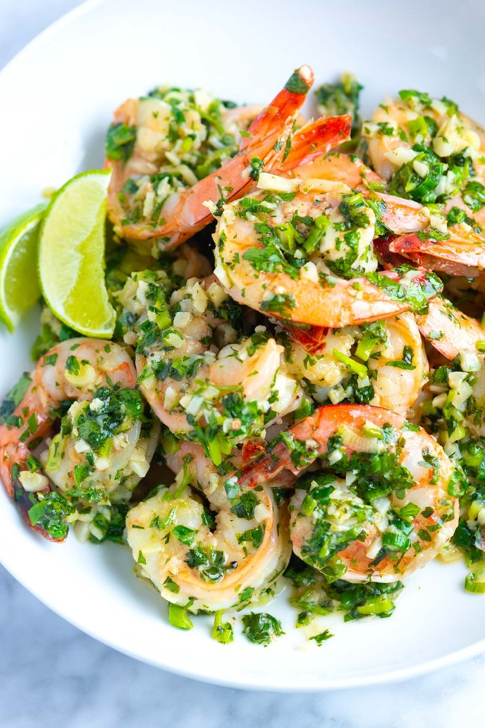 seasoned jumpo prawns, with chopped fresh green herbs, hors dourves, inside a white plate, with lemon and lime wedges