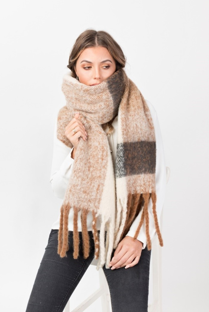 fluffy and soft, oversized beige woolen scarf, with white and grey pattern, and long brown tassels, wrapped around the neck and mouth, of a young brunette woman