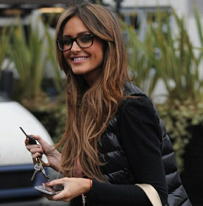 smiling slim woman, dressed in black, and wearing black-framed glasses, long balayage dark hair with layers