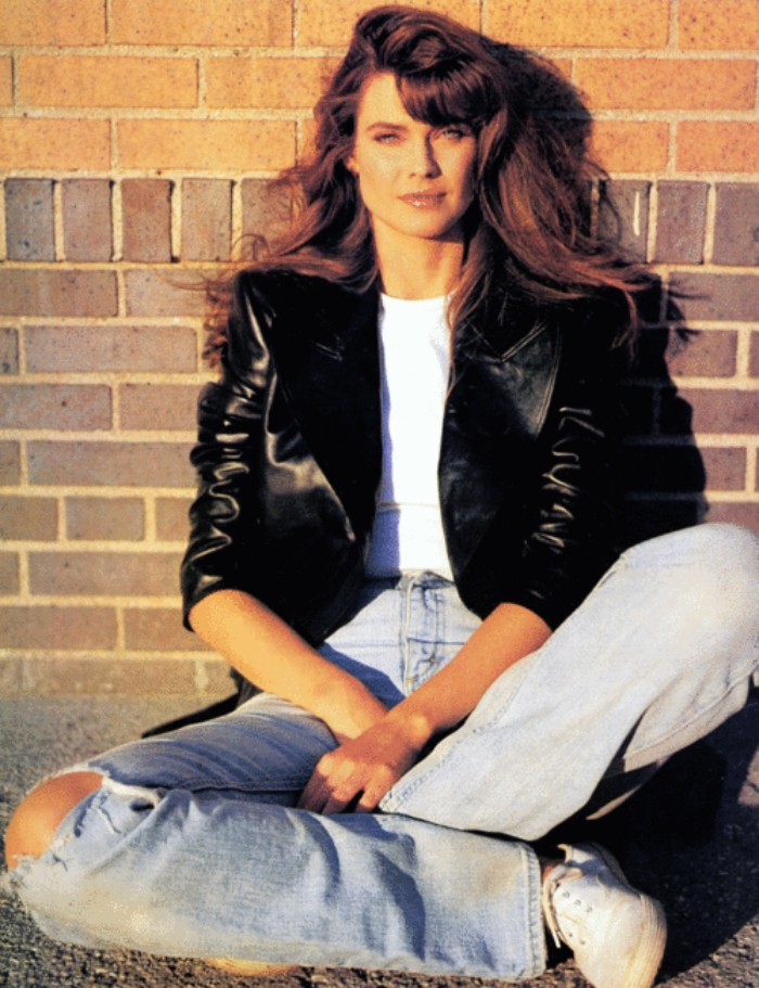 80's fashion pictures, young woman with long, wavy brunette hair, dressed in sidtressed high waisted jeans, a white t-shirt, and a black leather jacket