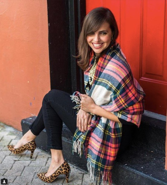 sitting slim brunette woman, dressed in black ankle jeans, with an oversized tartan scarf, wrapped around her shoulders, animal print stilettos and a pearl necklace