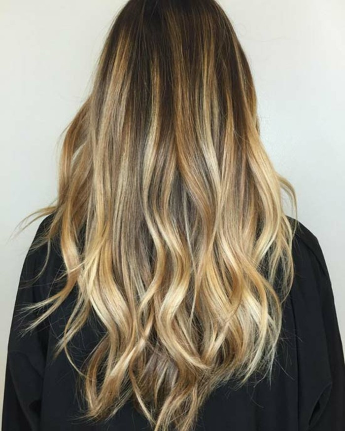 golden blonde bayalage, on long dark brunette hair, with loose curls, seen from the back