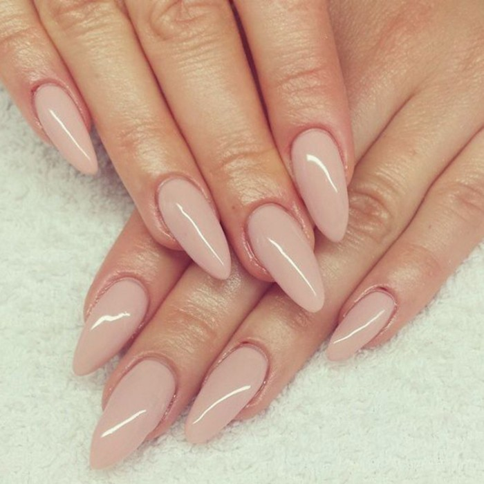 towel-like fabric, in off-white, under two hands, with long almond nails, painted in pale, nude pink polish