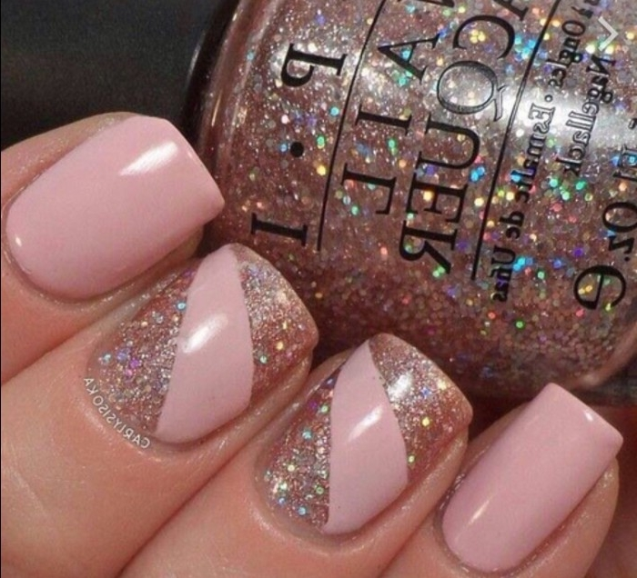 glass bottle of glitter nail polish, held by a hand with square nails, painted in nude pink, and decorated with multicolored glitter