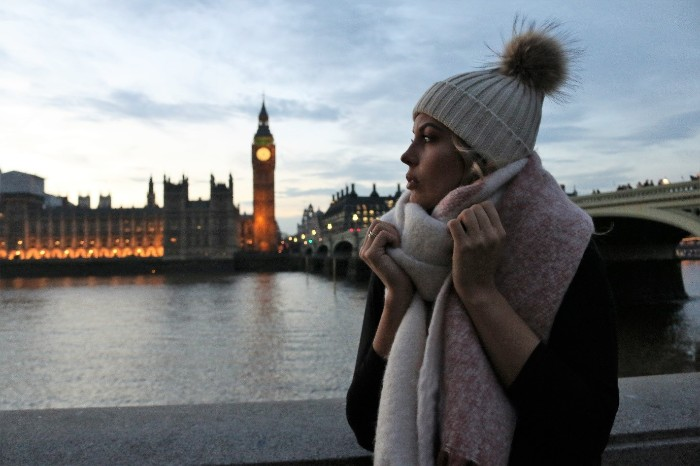 big ben in the evening, near a woman, dressed in winter clothing, knitted beanie hat, with a fur pom pom, large soft scarf around her neck, how to fold a blanket scarf