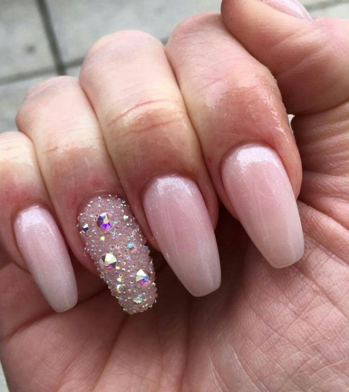 slightly sparkly nude pink nail polish, on coffin shaped manicure, the ring finger nail is covered in 3D, gem decal stickers