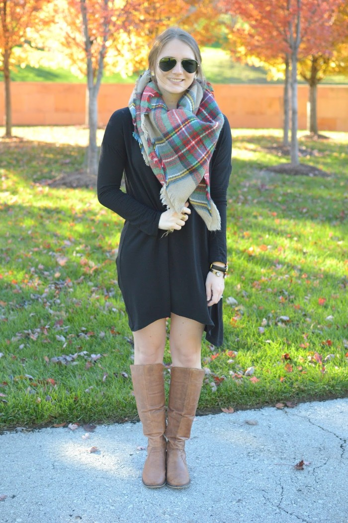 mini dress in black, worn with brown leather boots, and a checkered scarf, by a smiling blonde woman, with dark sunglasses, ways to wear a blanket scarf, fall scene in the background