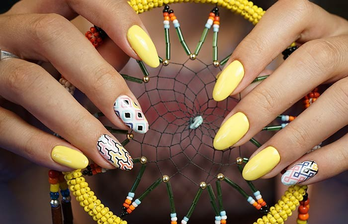 yellow acrylic nail shapes, some decorated with colorful patterns, on two hands, holding a dream catcher