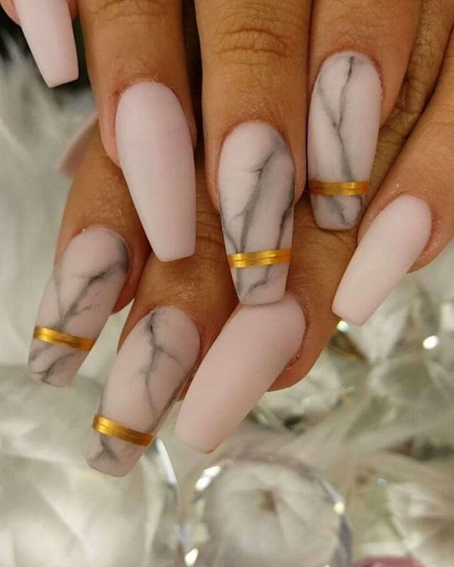 nude matte nails, with long ballerina shape, four decorated with a grey, marble-like pattern, and gold stripes, and four left plain