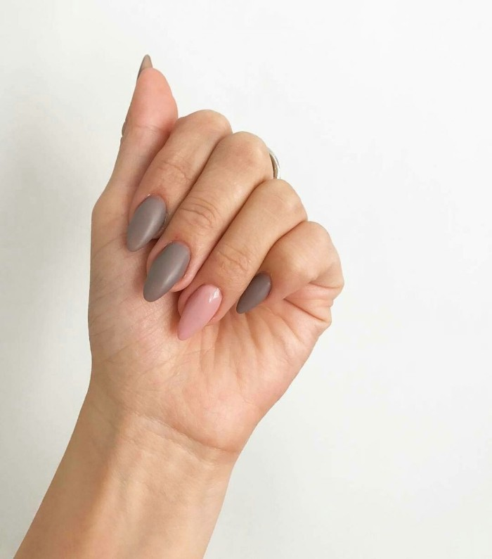 hand with folded fingers, and medium to short pointy nails, painted in creamy grey, and pastel pink nail polish