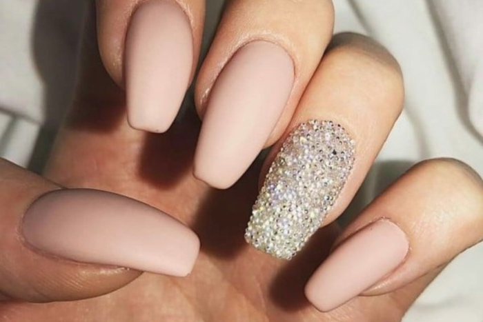 nude nails with glitter, long ballerina shape, and pale pastel pink matte nail polish, on a hand with folded fingers