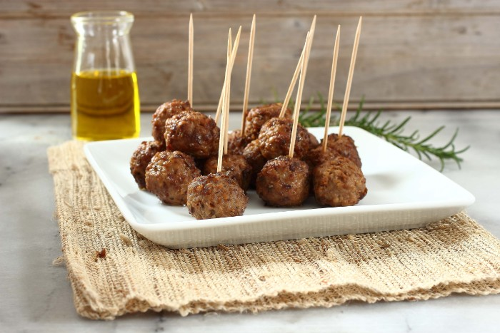 cocktail meatballs on a white dish, hor d oeuvres with meat, a clear bottle of olive oil in the background