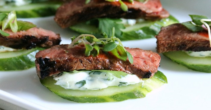 beef pieces medium rare, on top of cucumber slices, with a yoghut spread, hor dourves garnished with watercress