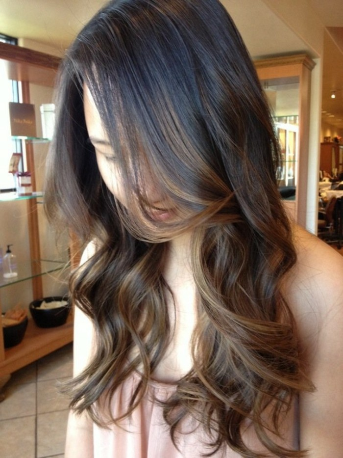 loose curls in chestnut brown, on medium length hair with dark roots, balayage brown hair, worn by a woman in a pale pink top
