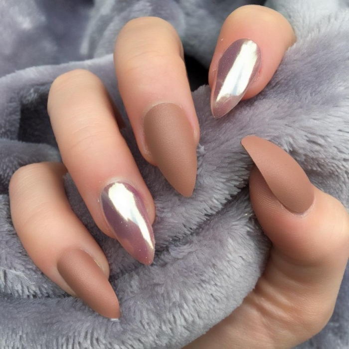 claw-like manicure, on a hand holding a fluffy, pale grey fabric, three dark nude gel nails, and two pink metallic nails
