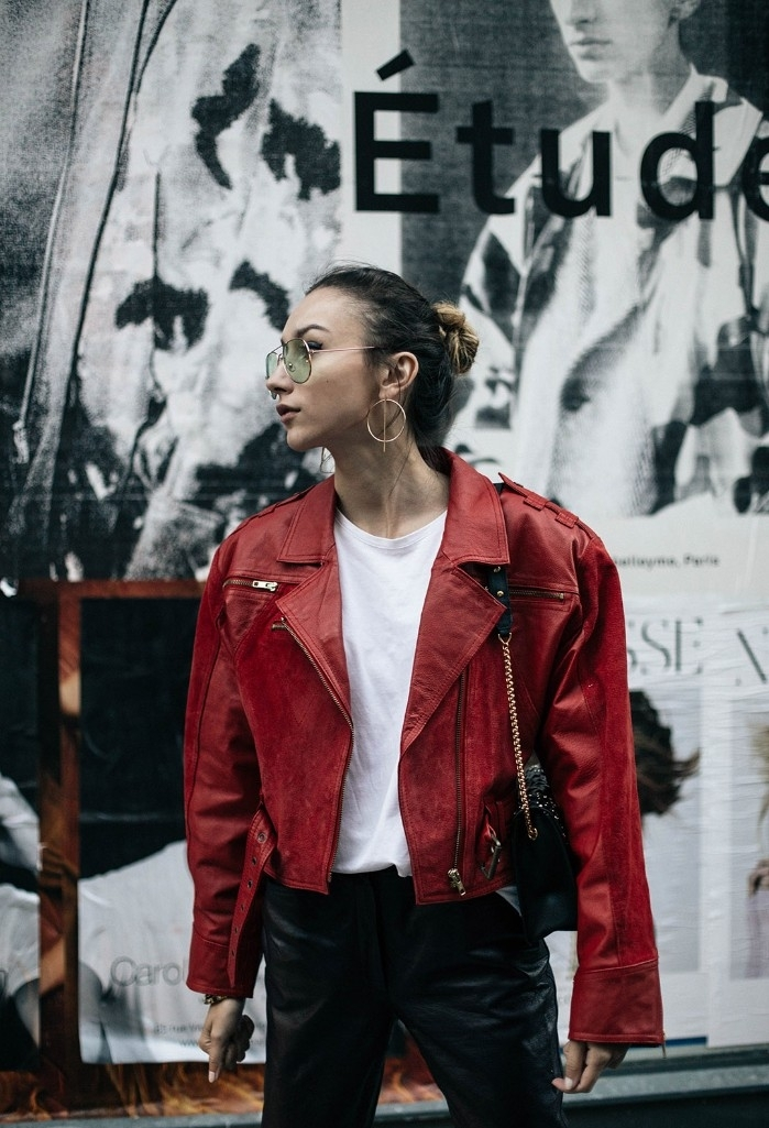 red leather jacket, inspired by michael jackson, worn over a white top, and black leather trousers, 80s outfits, on a young woman