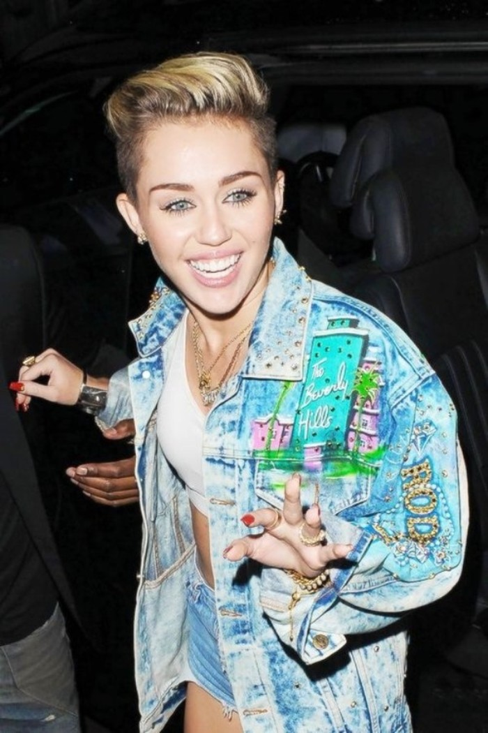 applique details and patches, on an oversized denim jacket, worn by miley cyrus