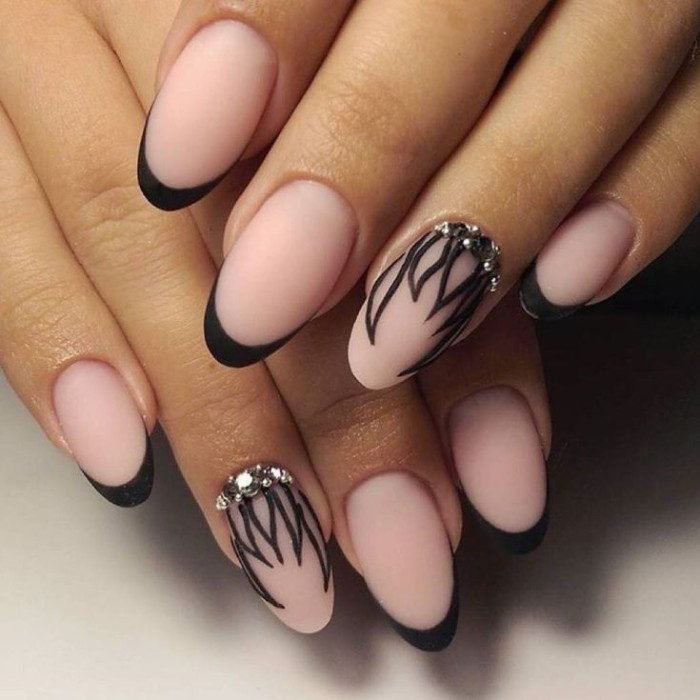 rhinestones and black, hand-drawn leaf-like patterns, decorating the ring finger nails, of two hands with nude manicure, featuring black tips