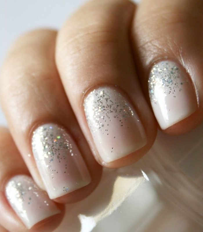 extreme close up of four, short square nails, covered in milky pink, best nude nail polish, decorated with silver glitter
