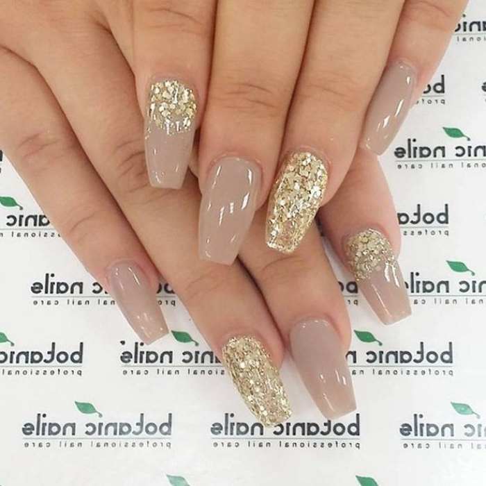 beige nude nail polish color, on a coffin shaped manicure, decorated with gold glitter flakes