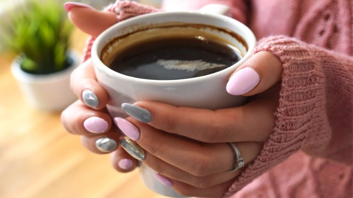full coffee mug, held by two hands, with almond shaped nails, painted in pastel pink, and creamy grey