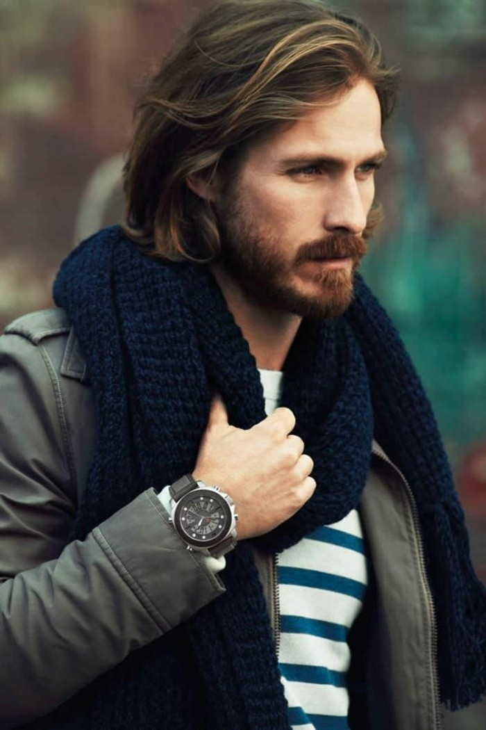 modern haircuts for men, medium length brunette hair, wavy with natural-looking highlights, worn messily slicked back, by a bearded man with a mustache