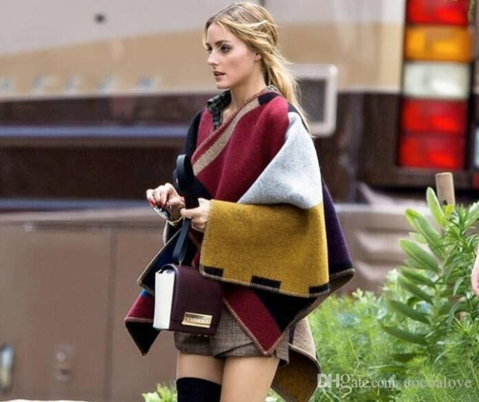 block colored oversized scarf, worn like a cardigan, by a slim young blonde woman, in beige woolen shorts