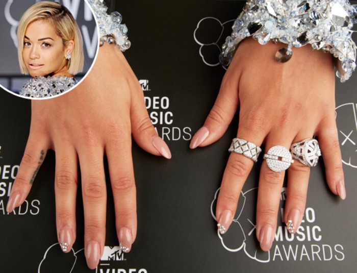 rita ora's manicure, nude pink oval nails, decorated with rhinestones, on hands decorated with chunky silver rings, and big bracelets