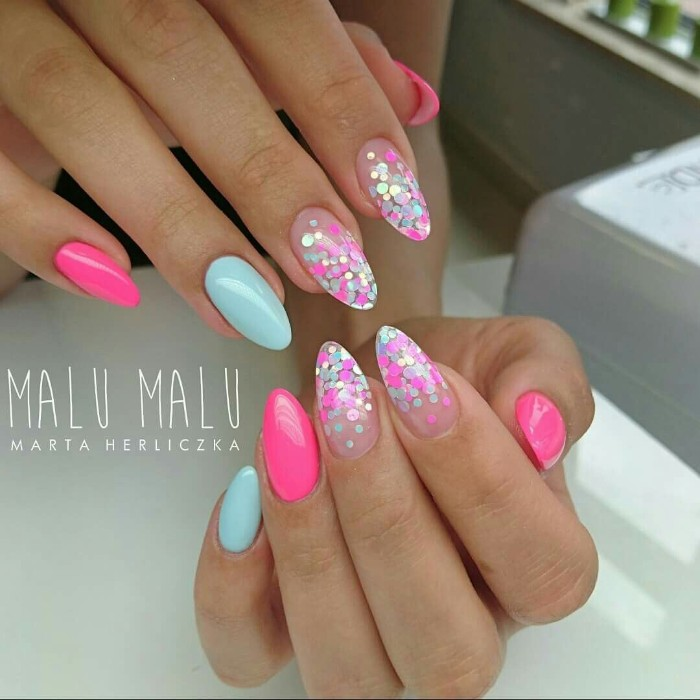 turquoise blue and neon pink nail polish, on two hands with oval shaped nails, four of the nails are nude pink, and decorated with iridecent neon pink, and neon blue glitter flakes