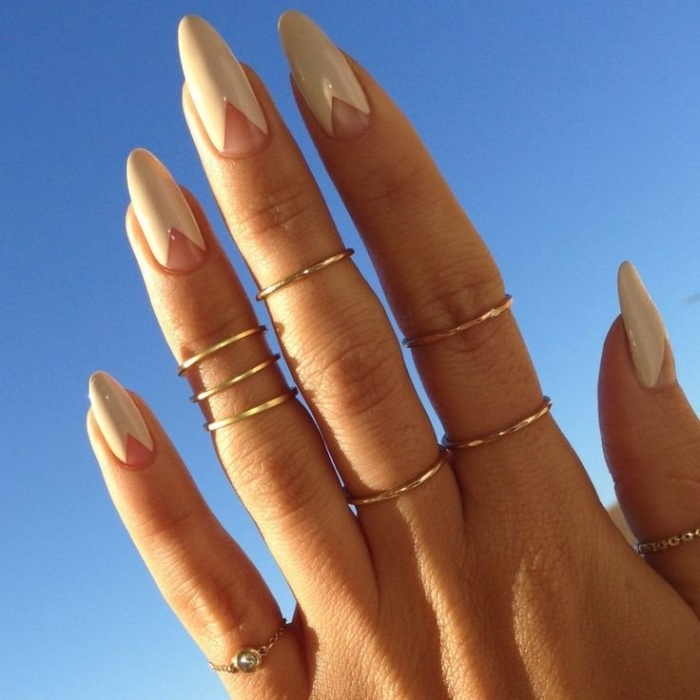 many thin gold rings, on a hand with long fingers, ending in pointy oval nails, nude nail designs, featuring small bare triangles