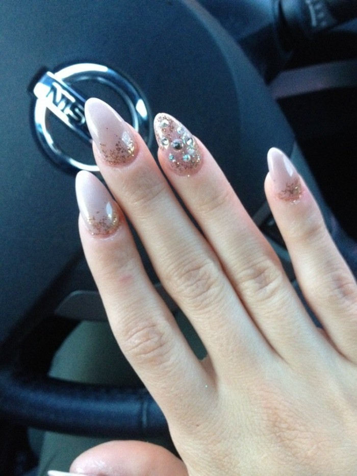 pointy nails, painted in pale pink, and decorated with glitter and rhinestones, on a hand, suspended over a steering wheel