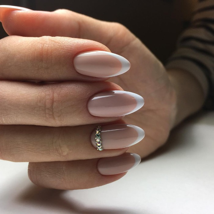 almond shaped nails, in pale nude pink, with white tips, the ring finger nail is decorated with diamante decal stones