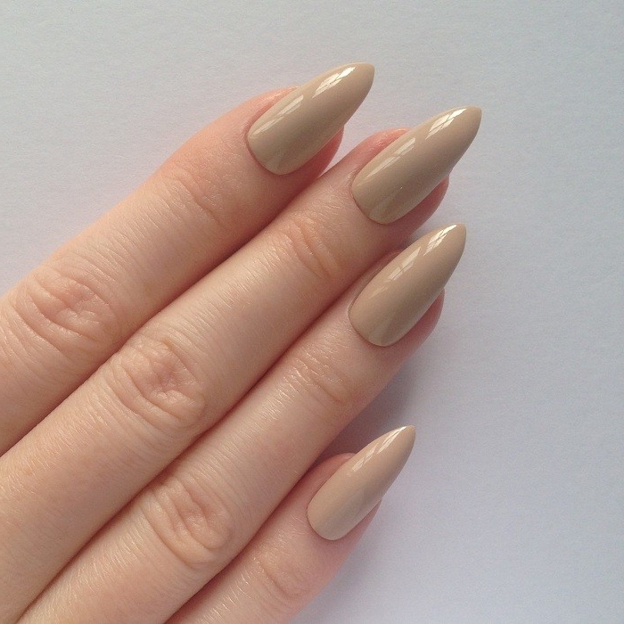 glossy and long, pointy oval nails, in a pinkish-beige color, nude nail designs, on long pale fingers
