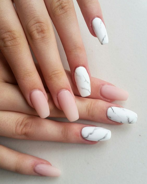 eight ballerina shaped nails, four are pink nude matte nails, and four have marble-like motifs in white and grey