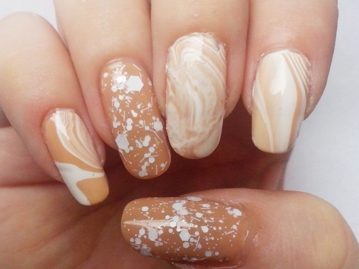 splatters and swirls of white nail polish, on long oval nails, in nude beige, nude nail designs